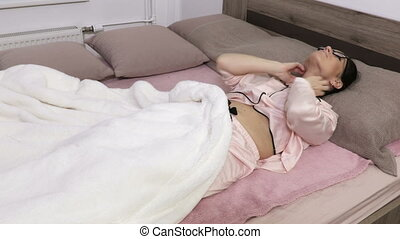 Woman lying on bed in pajama and scratching her itchy body.Healthcare and medical concept. Cause of itching from skin diseases