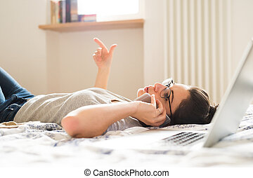 Woman lying on bed, working on laptop, calling. Home office.