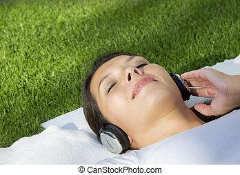 woman lying on blanket with headphones
