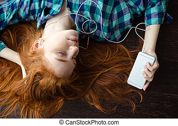 Woman lying on floor and listening to music