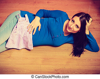 Woman lying on floor showing her pregnant belly