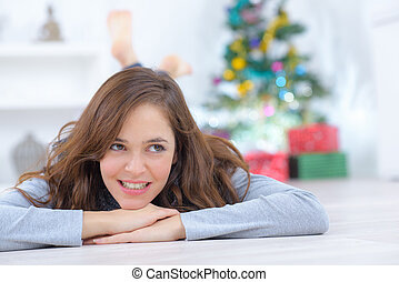 woman lying on floor with near christmas tree