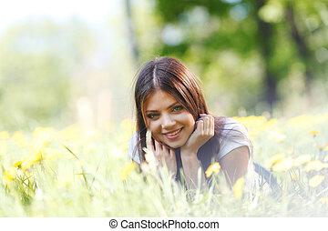 Woman lying on grass - Beautiful young woman lying on grass ...