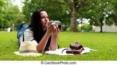 Woman lying on grass using camera
