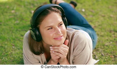 Woman lying on her front listening to music