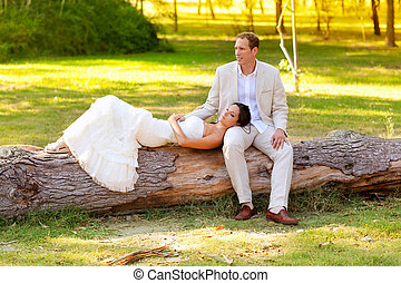 woman lying on husband leg in a park trunk