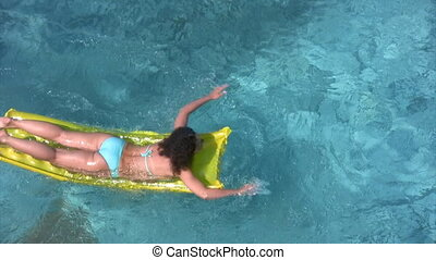 woman lying on inflatable mattress and oaring in water pool...