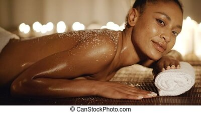 Woman Lying On Massage Table With Salt Scrub - Smiling young...