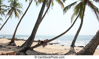 Woman lying on palm tree.