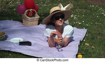 Woman lying on picnic blanket and drinking