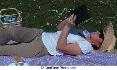 Woman lying on picnic blanket and reading book