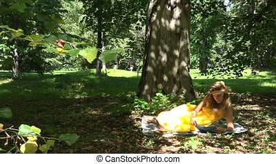 woman lying on plaid and reading books in park on beautiful sunny summer day. 4K