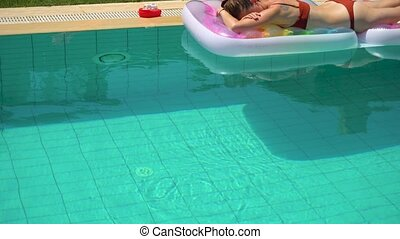 Woman lying on pool float on vacation - Female in brown...