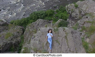 Woman lying on rock - From above view of casual woman lying...