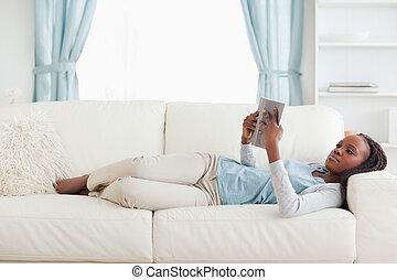 Woman lying on sofa reading