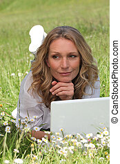 Woman lying on the grass and using her laptop