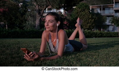 Woman lying on the grass listening to music on headphones with phone.