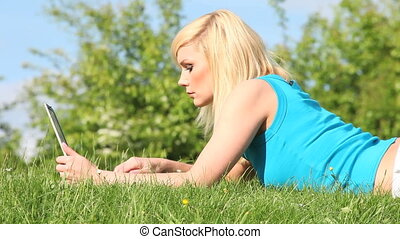Woman lying on the grass with a lap