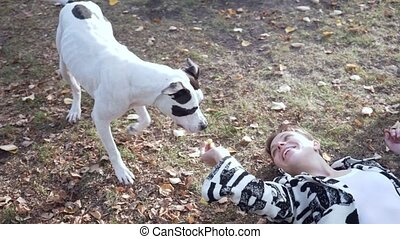 Woman lying on the ground and play with her stafford dog.