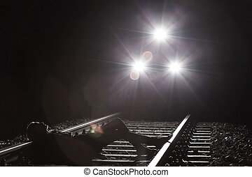 Woman lying on the railway tracks at the night