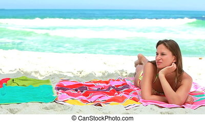 Woman lying on the towel as her friends join her