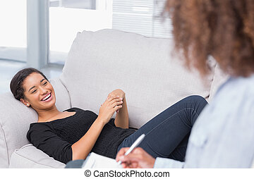 Woman lying on therapists couch looking happy as therapist...