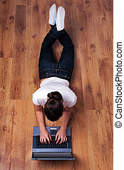 Woman lying on wooden floor using laptop