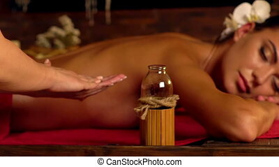 Close-up of hands masseuse with massage oil in spa salon. -...