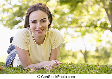 Woman lying outdoors smiling