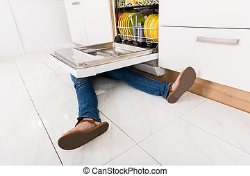 Woman Lying Under A Dishwasher - Close-up Of Young Woman Leg...