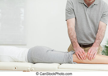 Woman lying while a man is massaging her calves