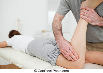 Woman lying while being massaged by a man