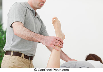 Woman lying while being stretched by a man