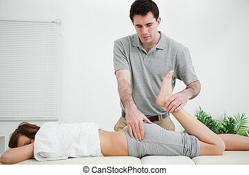 Woman lying while being stretched by a physiotherapist