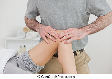 Woman lying with her legs folded while a man massaging her knee in a room