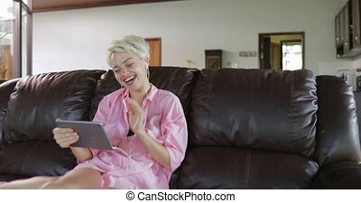 Woman Make Online Video Call Using Tablet Computer Sit On Coach In Living Room, Smiling Girl Speaking Internet Communication