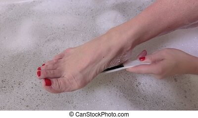 Woman make pedicure in bath