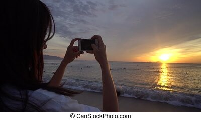 Woman make photo of beautiful sunrise over the ocean on smartphone.