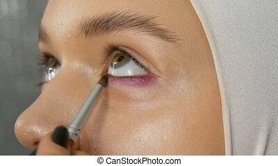 Woman make-up artist stylist makes makeup fashionable pink...
