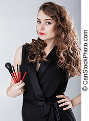 woman make-up artist with natural make-up holding makeup brush on gray background