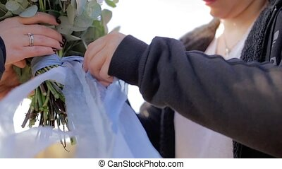 Woman makeing bridal bouquet outdoors at sunny day