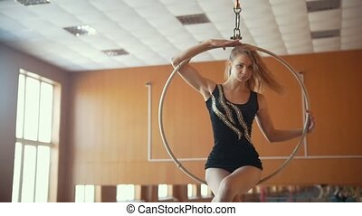 Woman makes a gymnastic elements on the aerial hoop -...