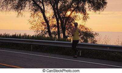 Woman makes an evening jog along the road along the lake. Steadicam follow shot