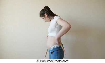 woman in white t-shirt makes measurements of the waist with a centimeter tape.