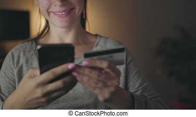 Woman makes online payment at home with a credit card and...
