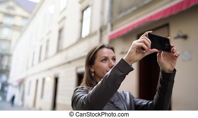 Woman makes photos attractions of the old city by the smartphone and strolls along the medieval street