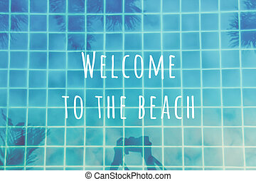 Woman makes pictures of palm trees reflection in the turquoise pool. Multipurpose backdrop with Welcome to the beach wording
