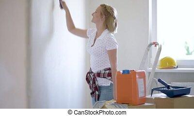 Woman makes repairs in flat - Young female makes repairs in...