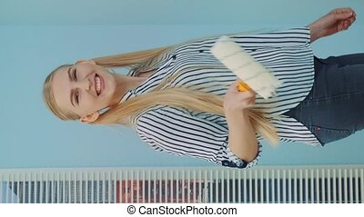 Beautiful woman makes repairs in the apartment dancing and smiling to the camera. She uses white paint and work with a roller. Office renovations. In the background there are skyscrapers at day. Video with Vertical Screen Orientation 9:16