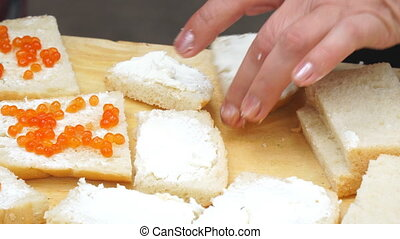 Woman makes sandwiches with red caviar and wheat bread